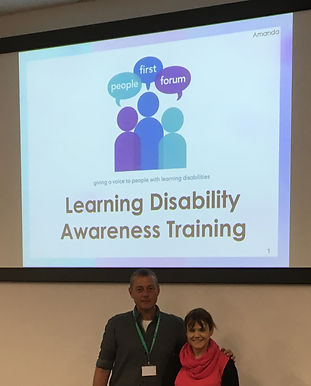 "An image of 2 members of the training team in a room. the 2 people are a man and a woman standing in front of a projected screen. the screen has the people first forum logo on it and the writing ""learning Disability Awareness Training"""