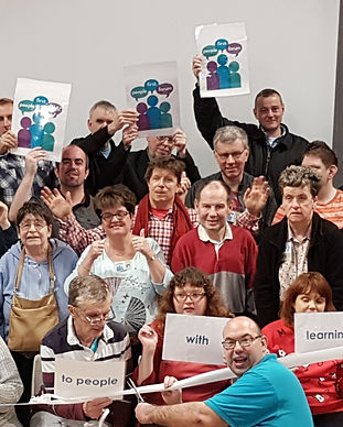 memebers stood in rows holding signs with People First Forum logos on at our launch day