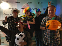 a group of clubbers using the props of a fun photo.  3 are wearing fun hats, 1 is wearing a colourfu