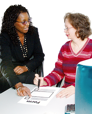 A lady supporting someone with learning disabilities to fill in a form