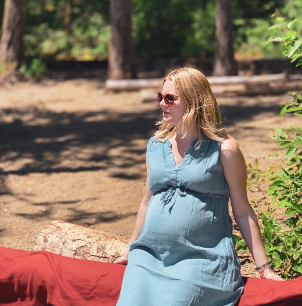 Pregnancy nutritionist wearing a blue dress sat in a forest with pregnant bump
