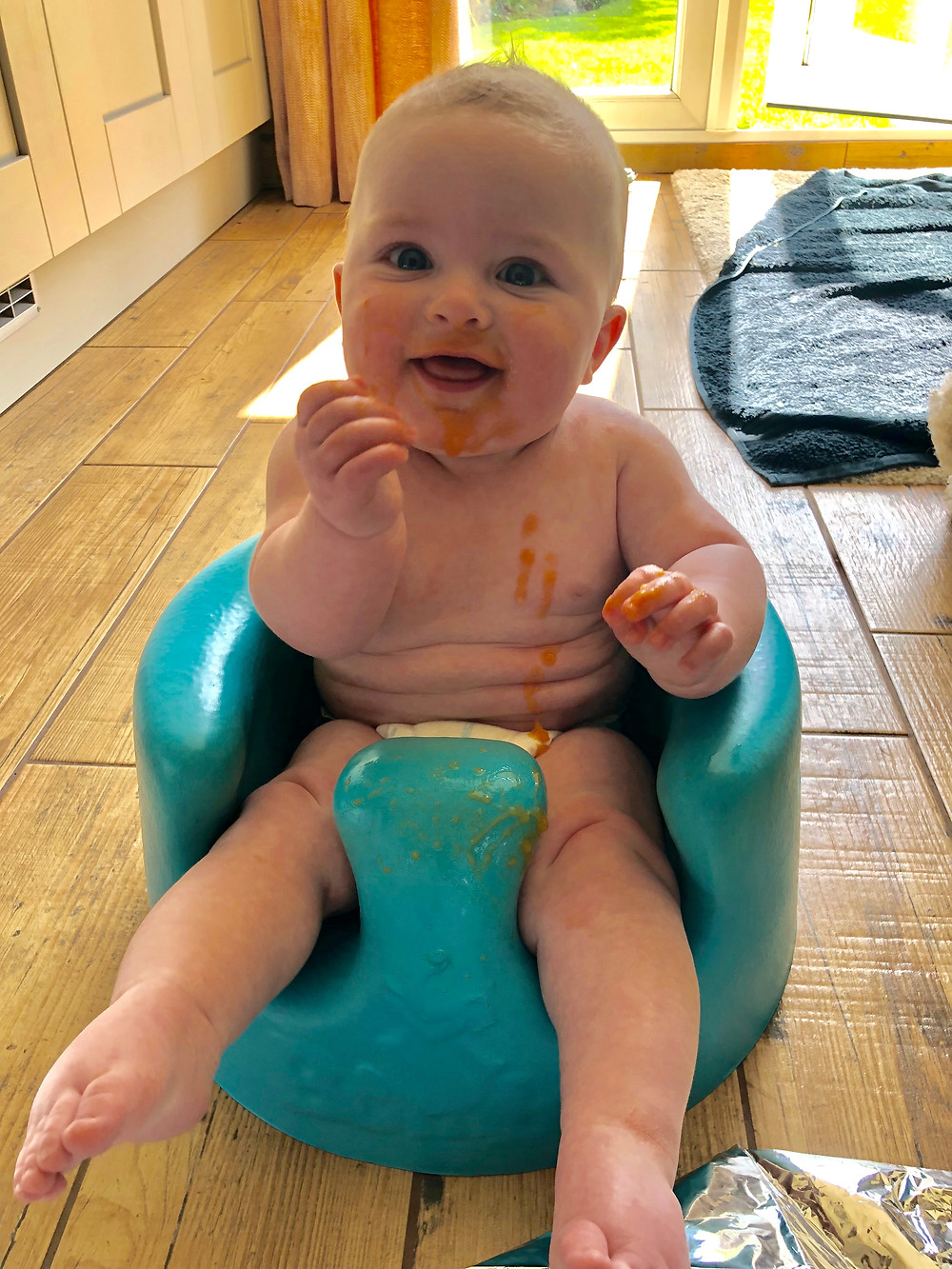 Premature baby in bumbo seat introducing solid foods and weaning