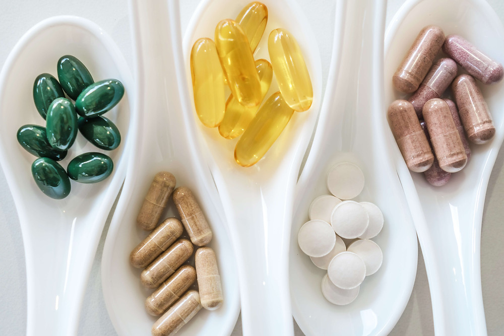 Pregnancy nutritionist vitamin supplements in spoons folic acid, vitamin D, omega 3 tablets and capsules