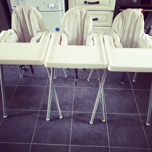 three white highchairs for weaning baby in a kitchen