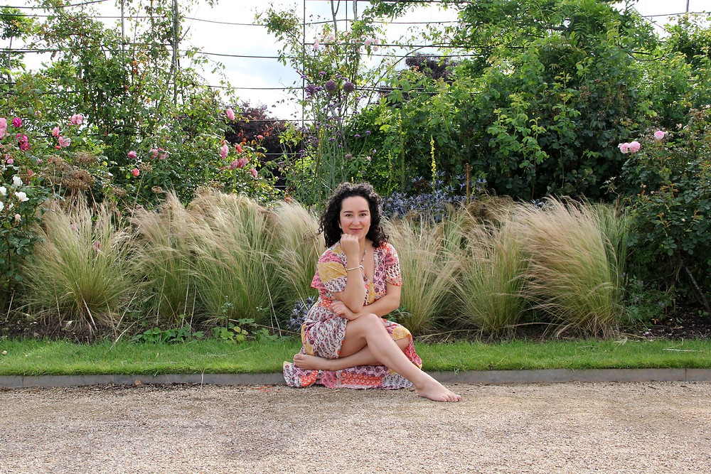 young single mum yoga pose surrounded by beautiful flowers