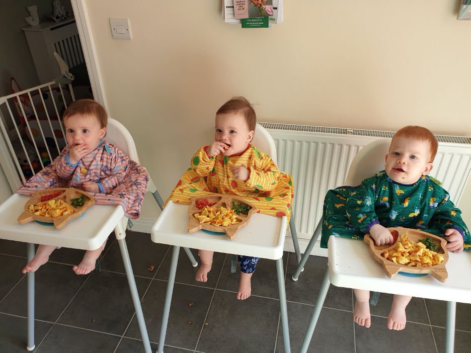 triplets sat in high chairs wearing bibs eating finger foods