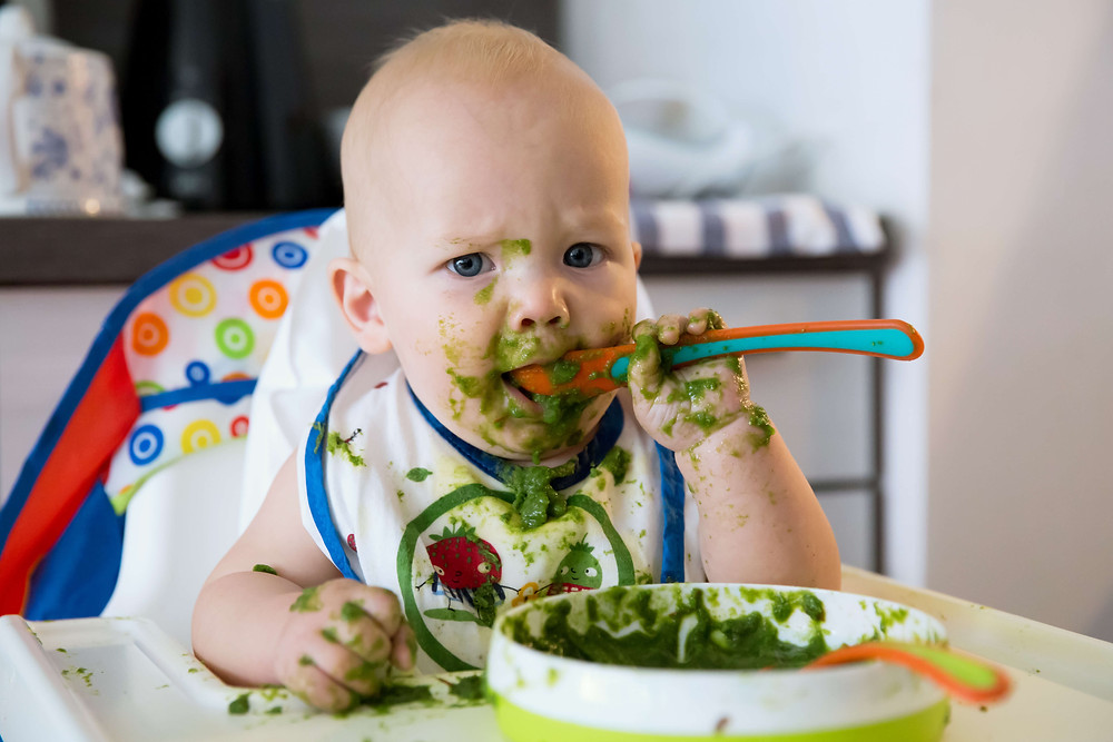 baby weaning with spoon and green veg as first weaning foods baby weaning class