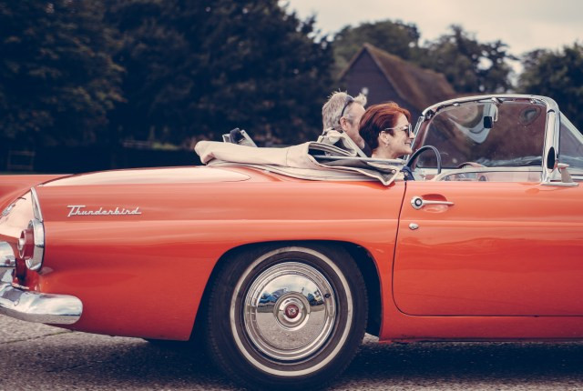Couple Riding Red Ford Thunderbird during Daytime