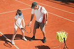 Tennis coach instructing young talented