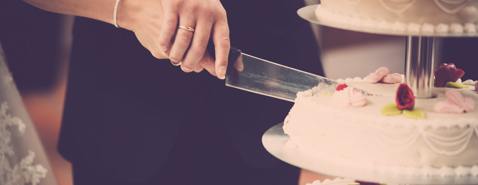 person-holding-knife-slicing-3-layer-cak