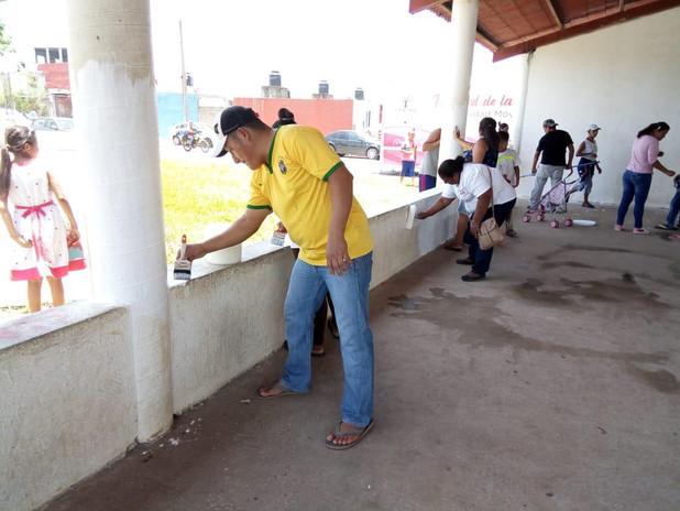 Vecinos pintando la palapa comunitaria.