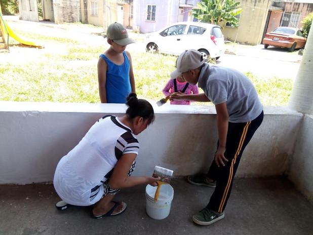 La comunidad pintando la palapa comunitaria.