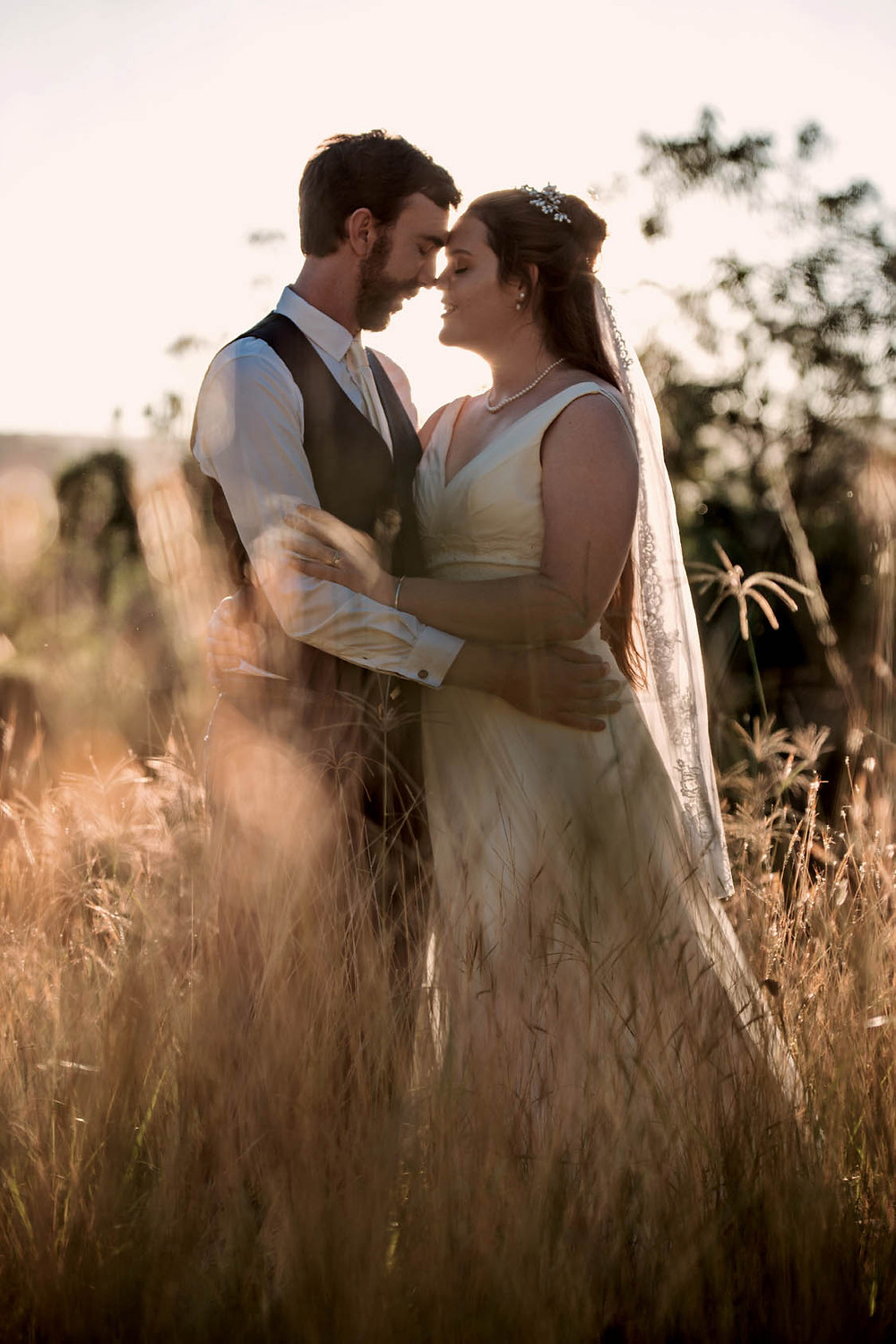 Couple in field in Hampshire at golden hour on their wedding day
