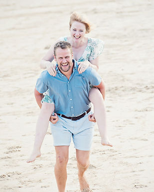 A couple newly married and the bride has jumped on to the grooms back. At the beach in Brigton, West Sussex