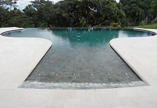 La piscine miroir se distingue par la particularité de son bassin : le niveau de ses quatre bords se situe au niveau de la plage. Afin que l'eau s'écoule de façon égale sur chaque bord, son bassin doit impérativement être rectangulaire. La piscine miroir arbore donc des lignes épurées et une démarcation discrète avec la plage. Et, comme son nom l'indique, son plan d'eau constitue un miroir reflétant joliment le ciel.