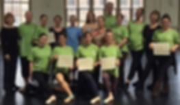 Teacher Certification Level C participants pose in their program t-shirts in tendu derrière with their partnering instructor Georgii Gusev in the center of the group.