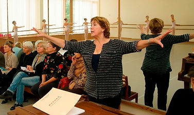 Bolshoi Ballet Academy teacher Vera Kulikova demonstrating the correct placement of the arms to a class of young female dancers who are being observed by a panel of adults.