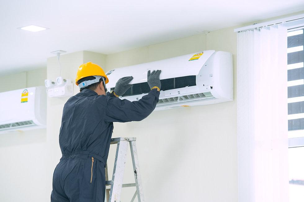 Maintenance engineer working on air conditioning unit.jpg