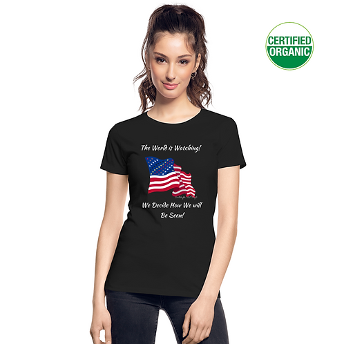 A girl wears a black t-shirt with the Civil Rights US flag on it, and the words The World is watching