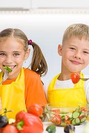 Happy children eat vegetables in the kit
