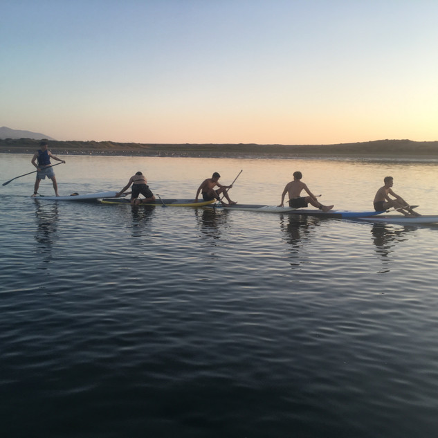 Stand up paddlers playing a game on paddleboards.