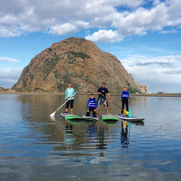 Four stand up paddlers in front of Morro Rock.