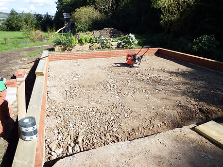 Compacting the hard-core with a Wacker plate compactor ready for the timber framed garages