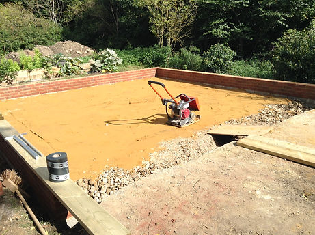 Compacting the sand blinding layer with a Wacker plate compactor for an oak framed garage
