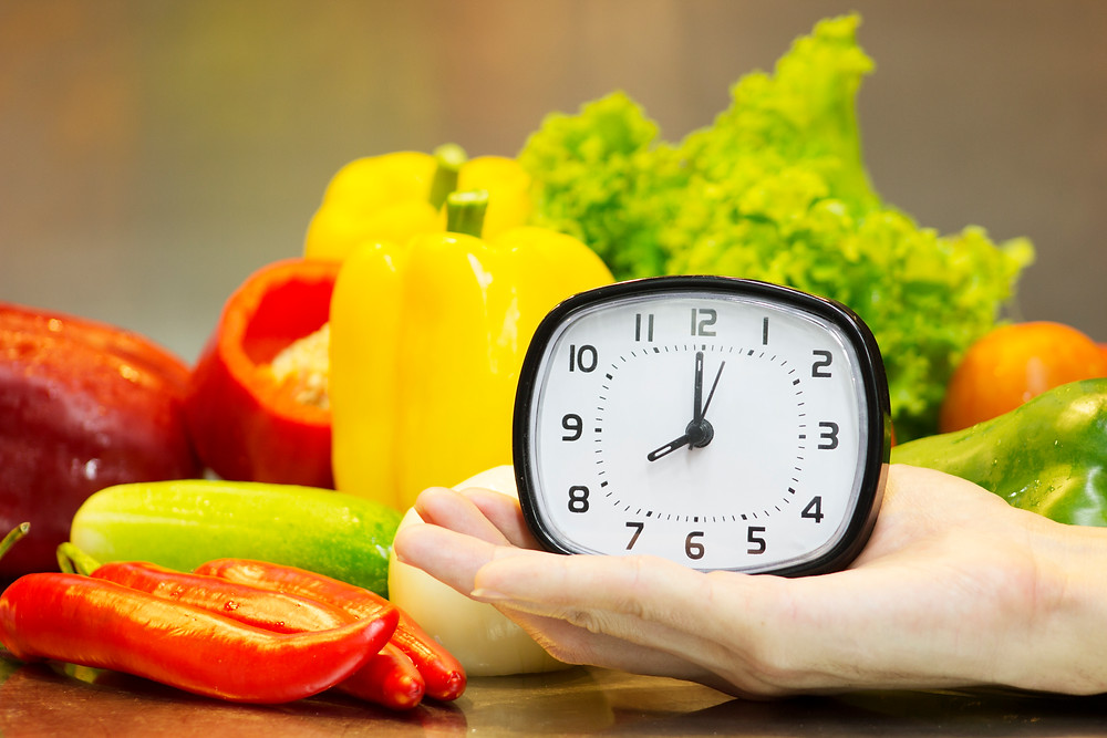 Clock and fresh vegetables showing the importance of regular meal-times.