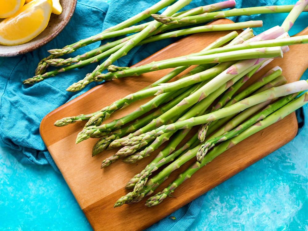 Fresh green asparagus on a wooden cutting board.