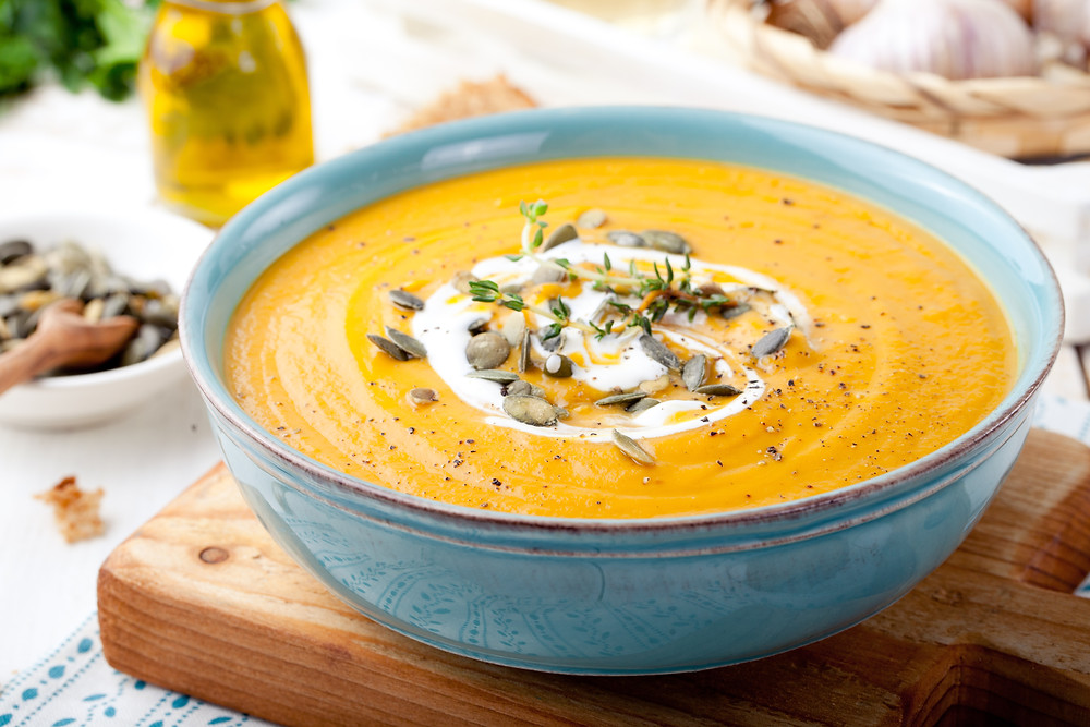 Bowl of carrot and pumpkin soup with cream and pumpkin seeds.