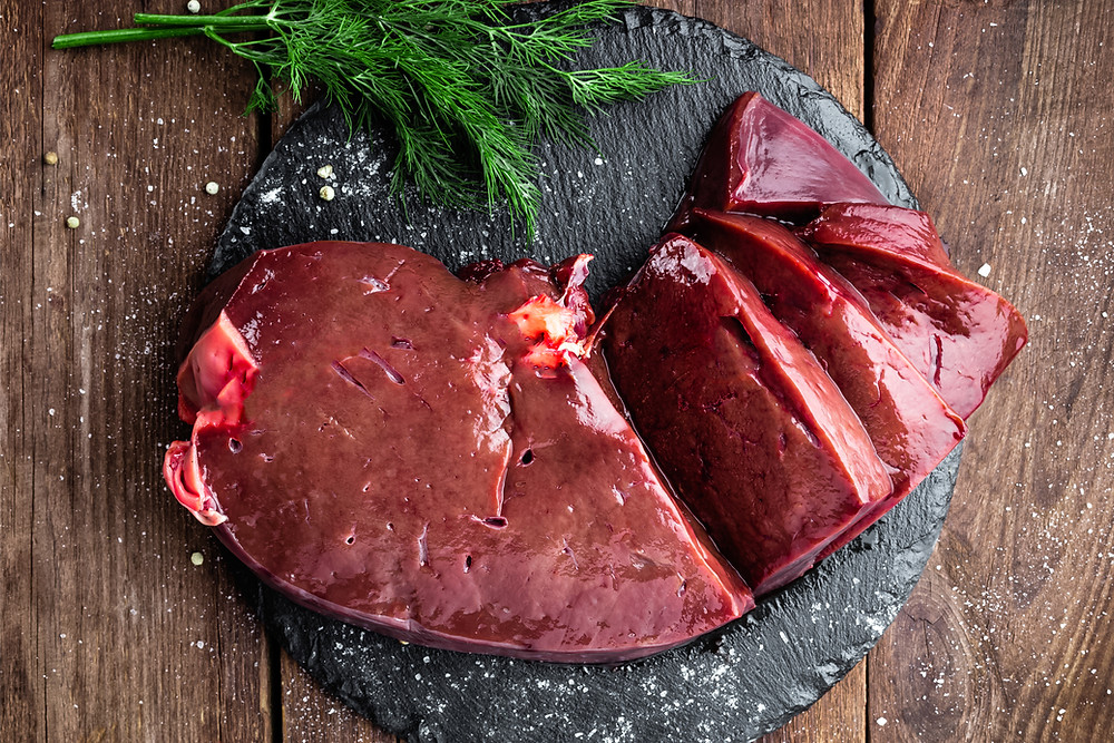 Raw liver on a black slab with sea-salt and a sprig of rosemary.