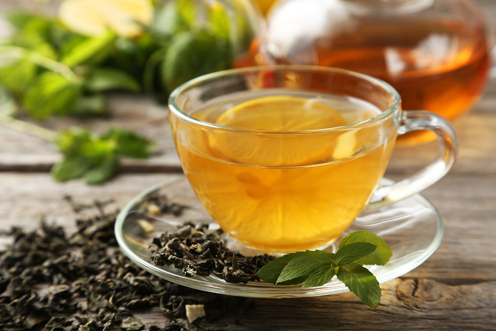Cup of green tea with lemon slice on a rustic background.