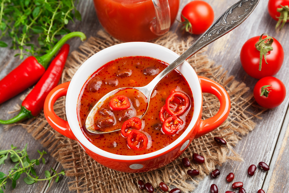 Bowl of chili with red chillies and tomatoes on a rustic wooden background