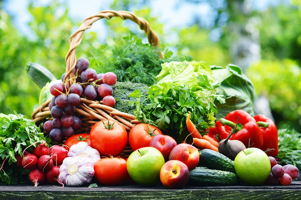 Basket of fresh fruits and vegetables in the countryside