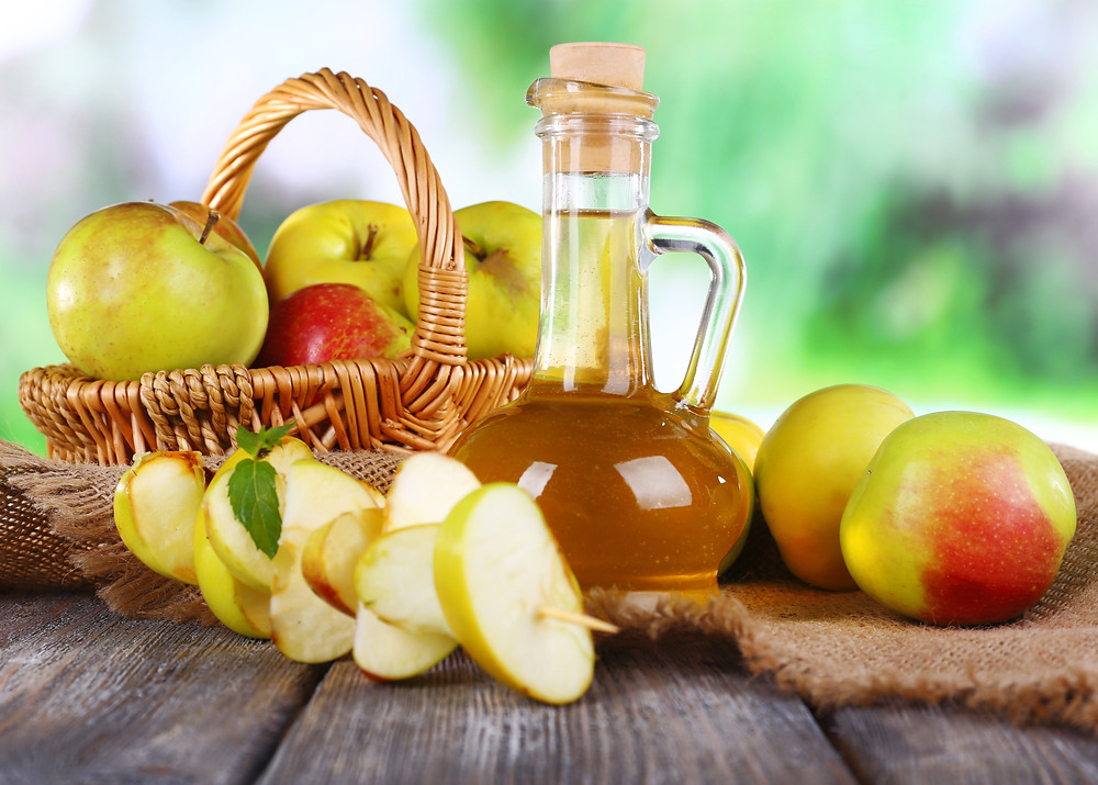 Apple cider vinegar and fresh green and red apples on a rustic wooden table.