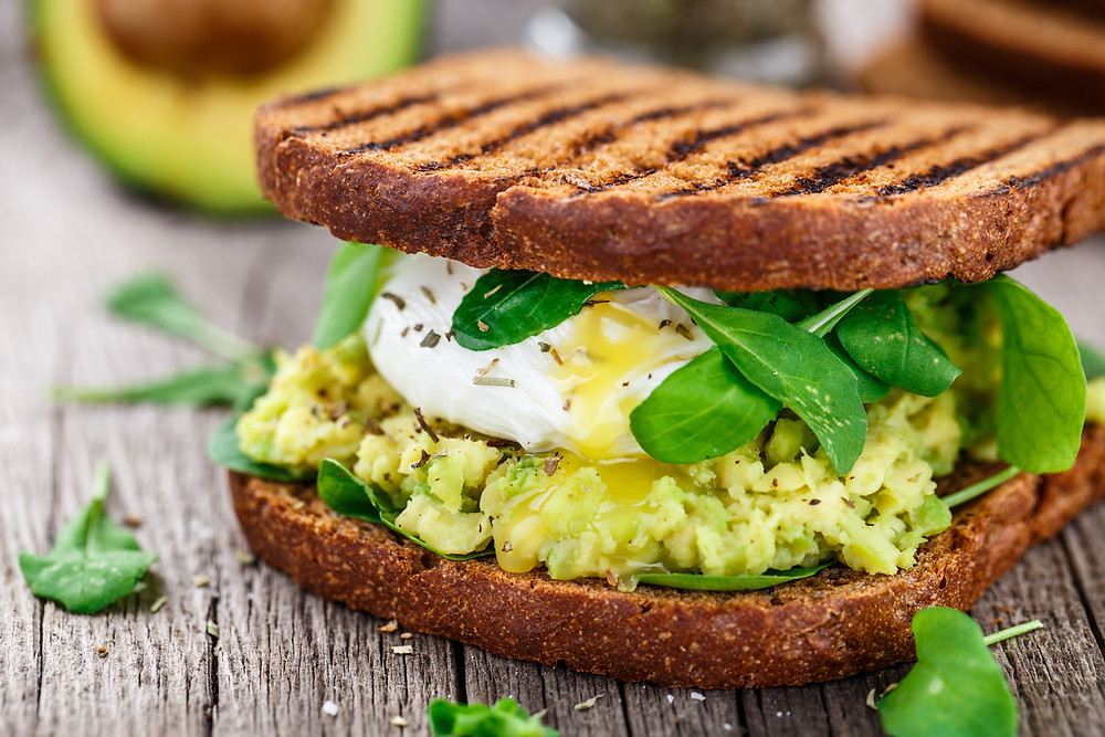 Avocado mash and poached egg between two slices of whole-grain toast on a rustic wooden background.