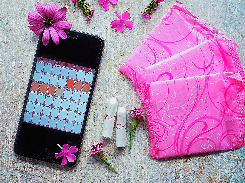Tampons, pink sanitary pads and smart-phone period calender on a stone background with pink gerberas.