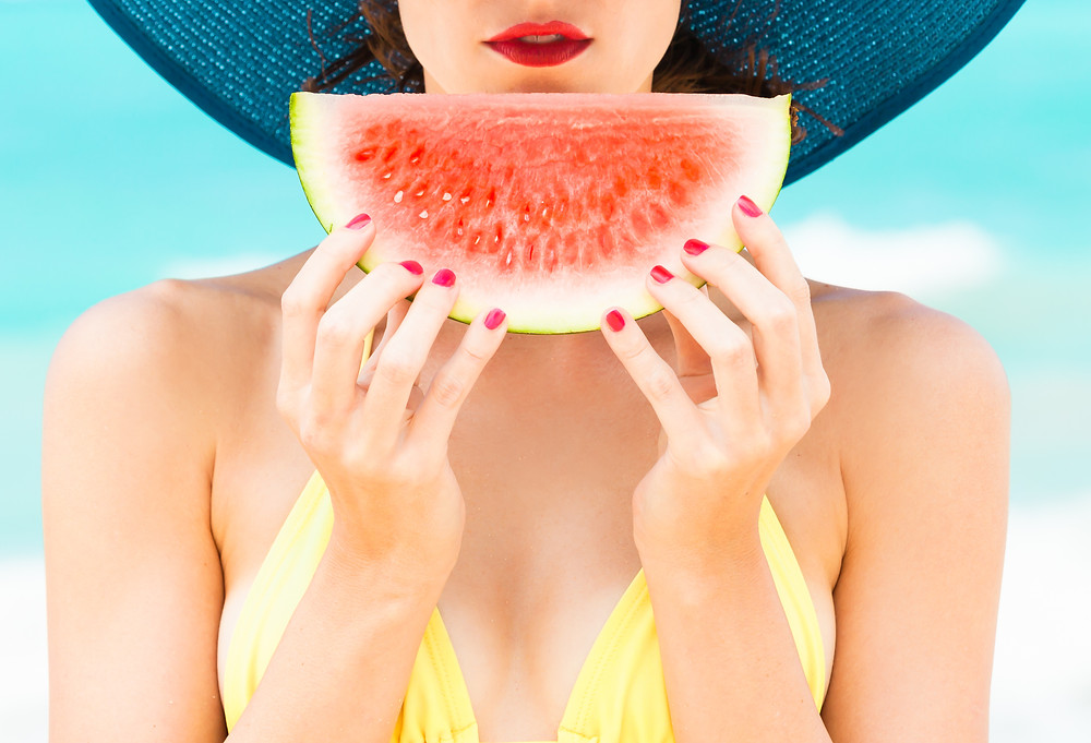 Woman wearing a hat holding a slice of watermelon in her hands.