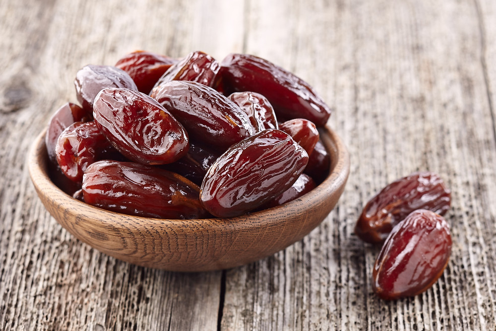 Bowl of Mediterranean dates on a wooden surface.