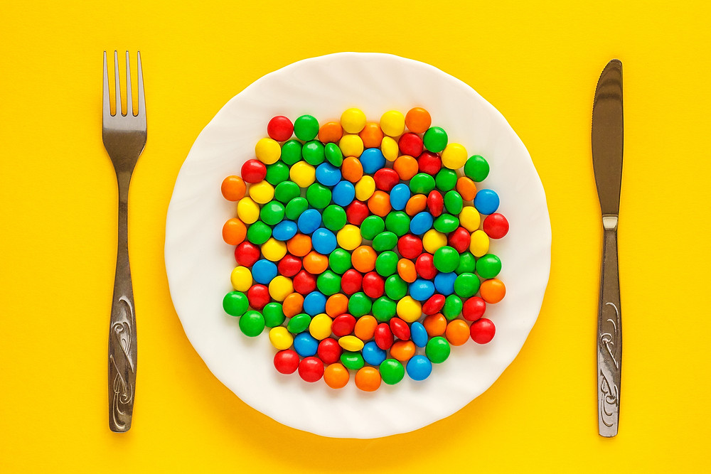 Plate of colourful candy on a cheerful yellow background with knife and fork.