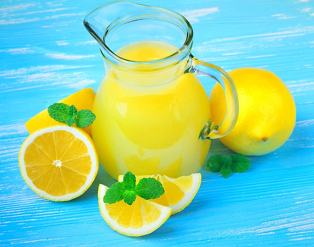 Hypochlorhydria and low stomach acid. Lemon juice and lemons on a blue background.