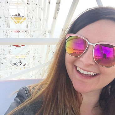 Emery on a Ferris wheel, wearing sunglasses and grinning
