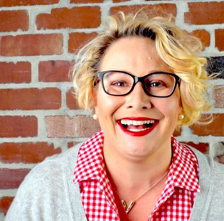 Happy, smiling blond woman with short curly bob, wearing eye glasses with black frames.
