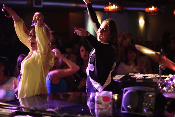 Two ladies singing and dancing on stage during a dueling pianos show