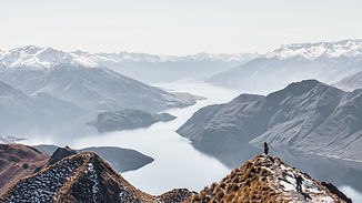 A videography lines up his shot at the tip of a mountain, the camera is shot from a drone over looking white mountains and blue lakes. The director is pointing out what they are seeing. This is in Christchurch New Zealand