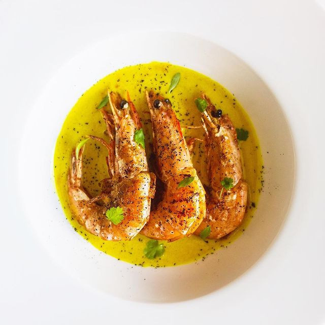 stefandining our seafood course for our new upcoming menu!  spiced prawns, coconut, saffron, vadouvan, @fresh_forage micro coriander, leek ash