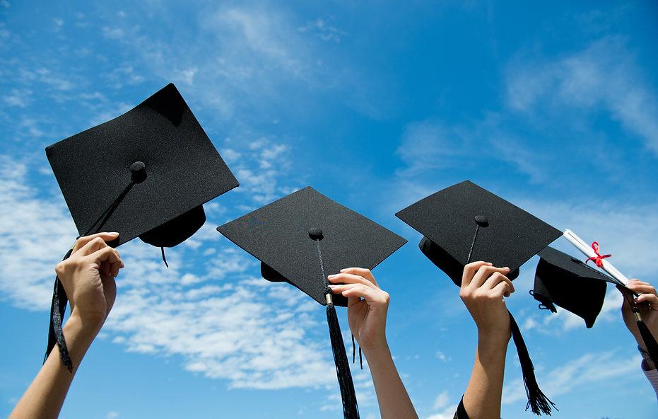 Many hand holding graduation hats on bac