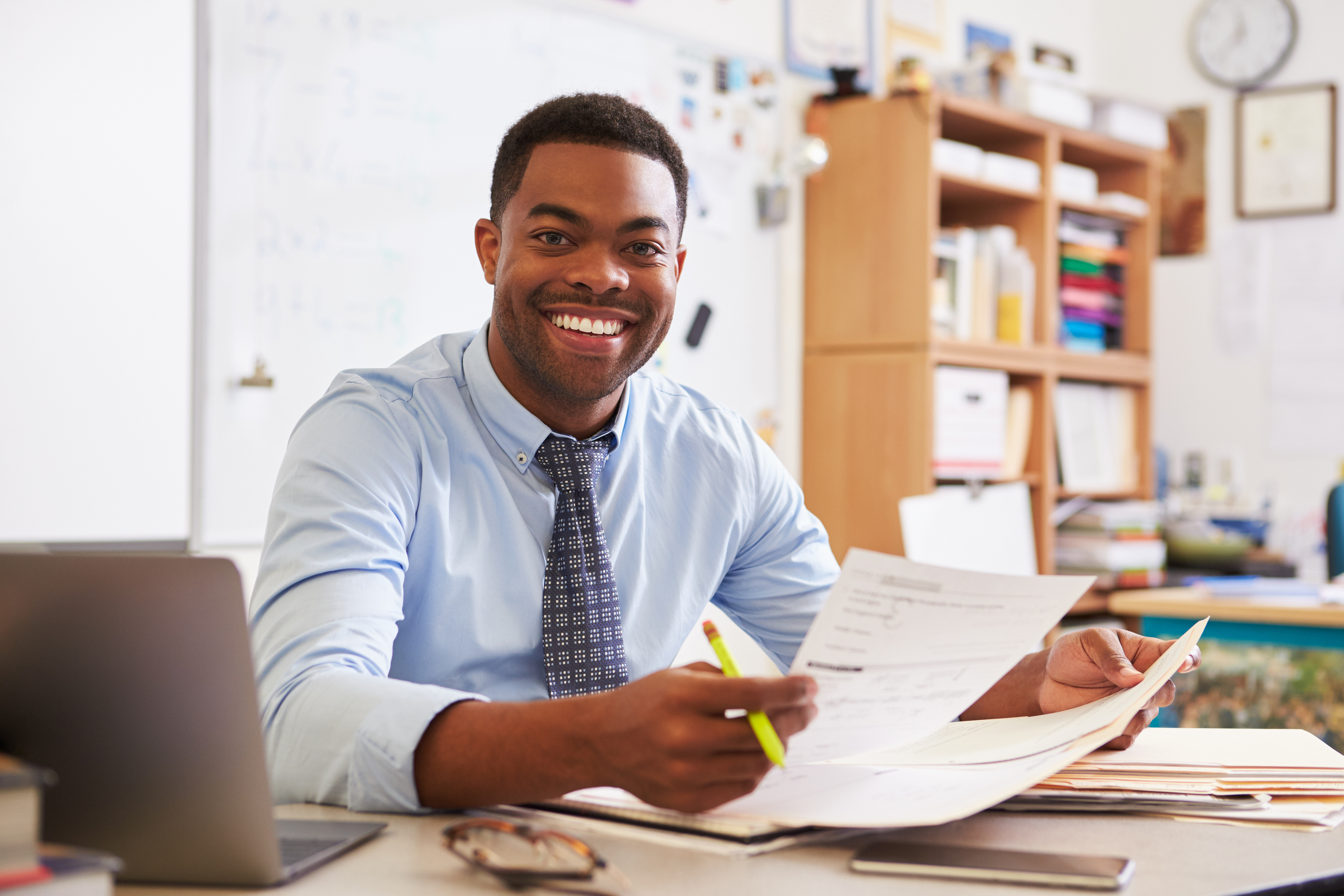 Portrait of African American male teacher working at desk