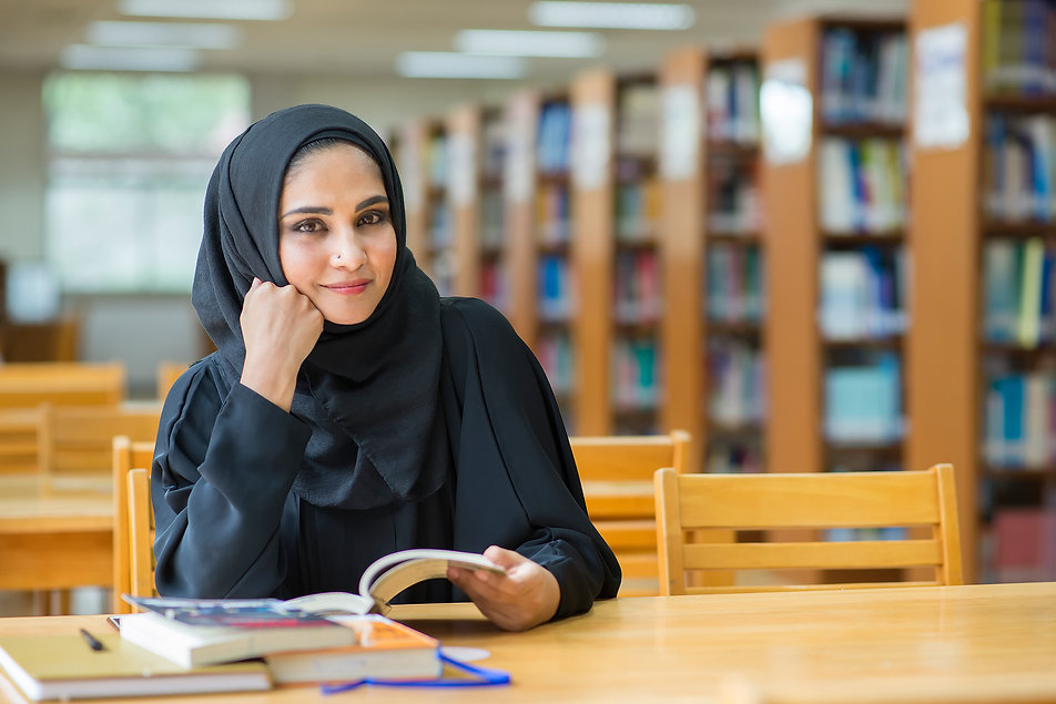 Muslim woman reading book at the library